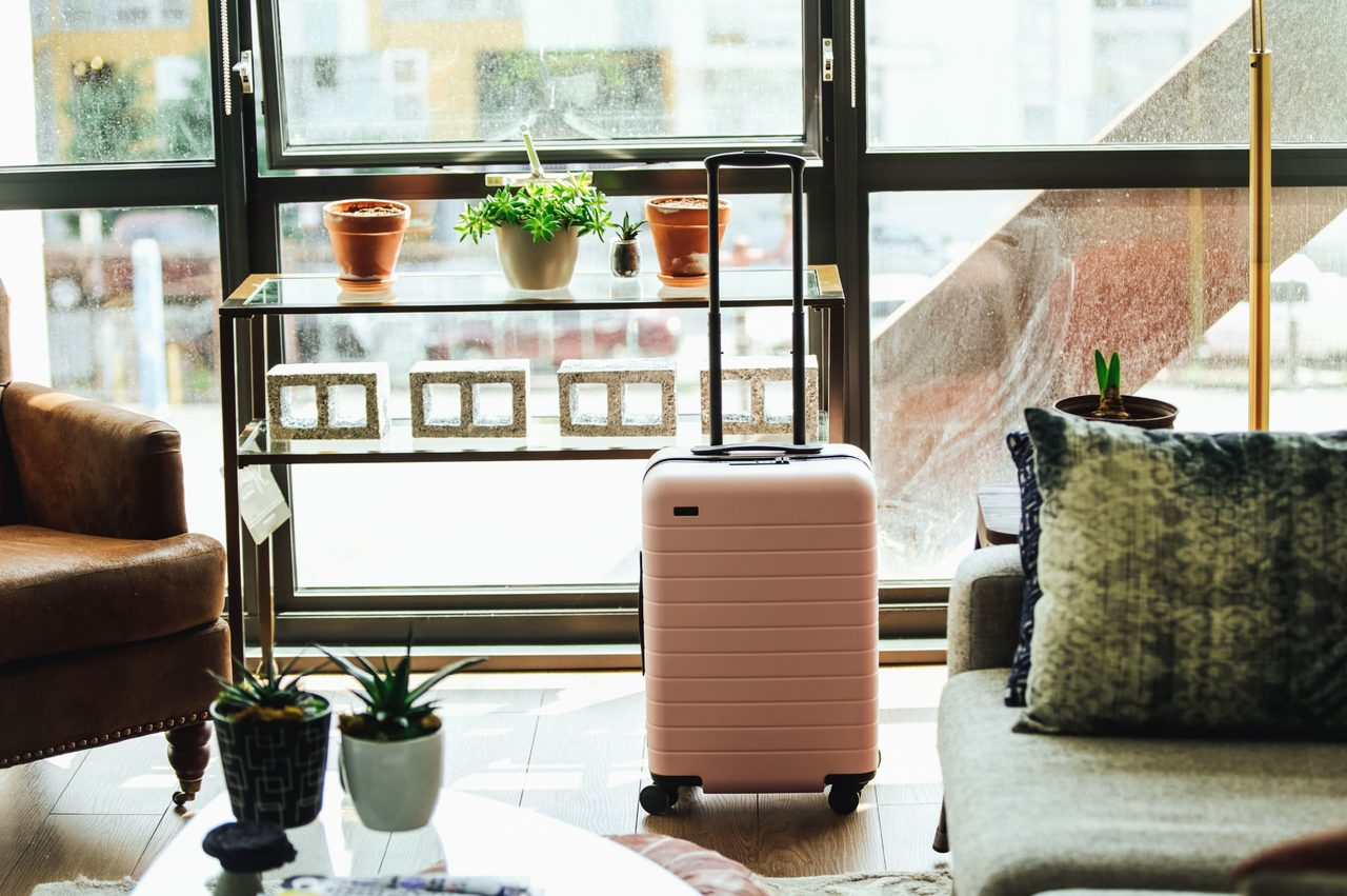 expats suitcase amongst rented furniture in new home