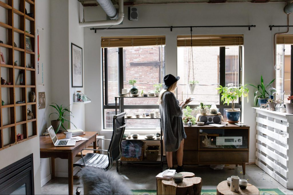 woman in home office with ergonomic chair, wooden furniture, and plants - casaone