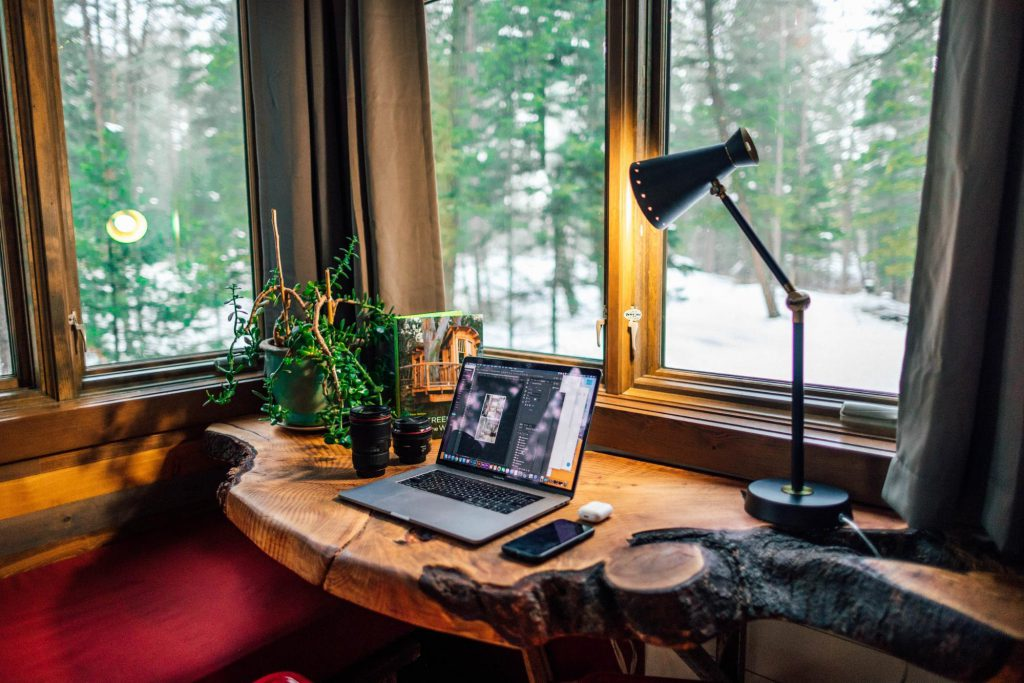 lamp shining on computer on wooden home office desk near window - casaone