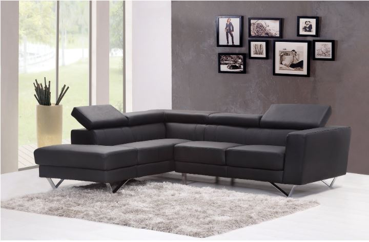 a living room setting with a sectional leather sofa & an area rug