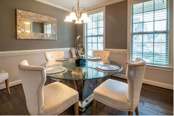 dining table with circular glass tabletop surrounded by fabric upholstered chairs