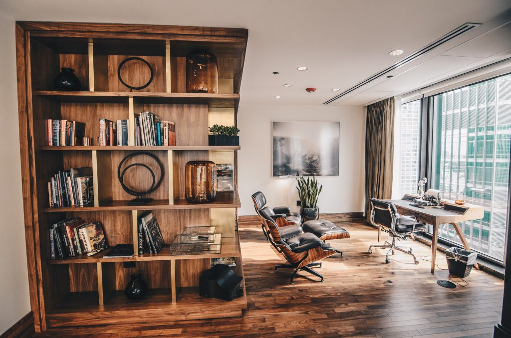A home office setting. A wooden desk & a task chair facing a large window, accompanied by the Eames Lounge Chair and a wooden bookshelf carved into the wall - an ideal environment for remote work.