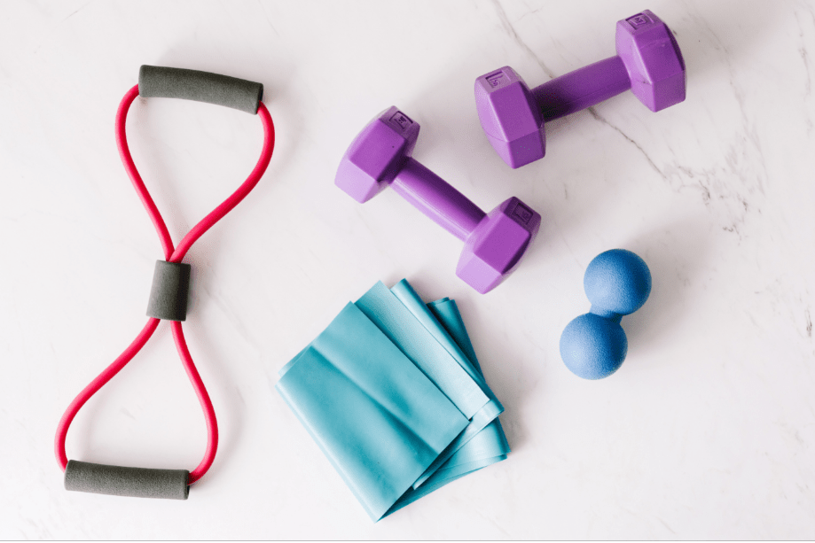 A couple of gym equipment including dumbbells placed on a marble surface