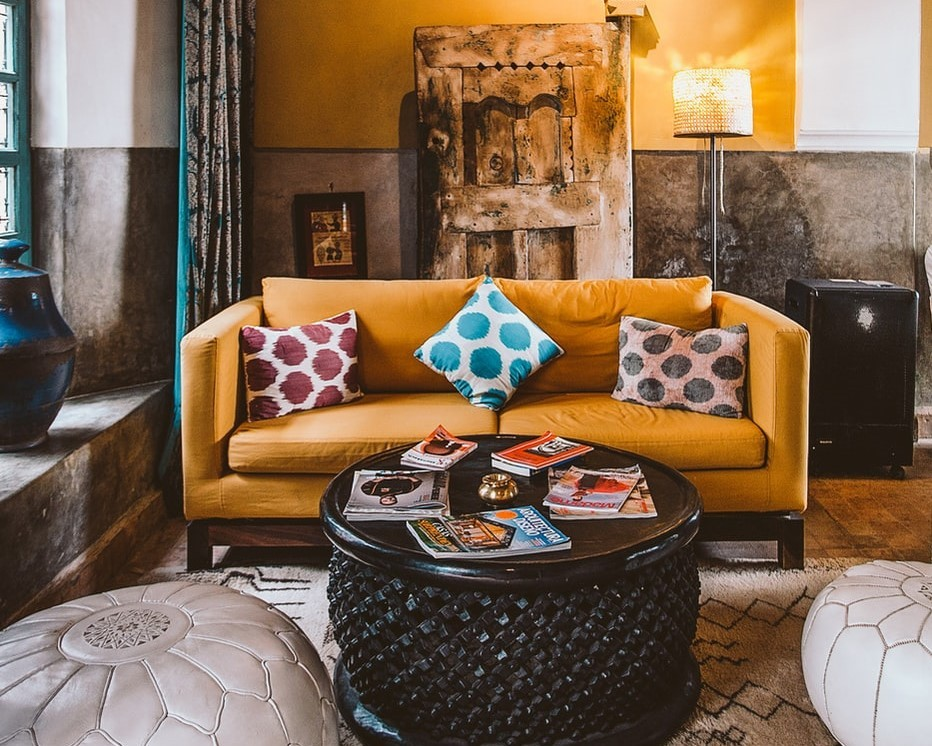 A cozy living room with a yellow couch and barrel-style wooden coffee table
