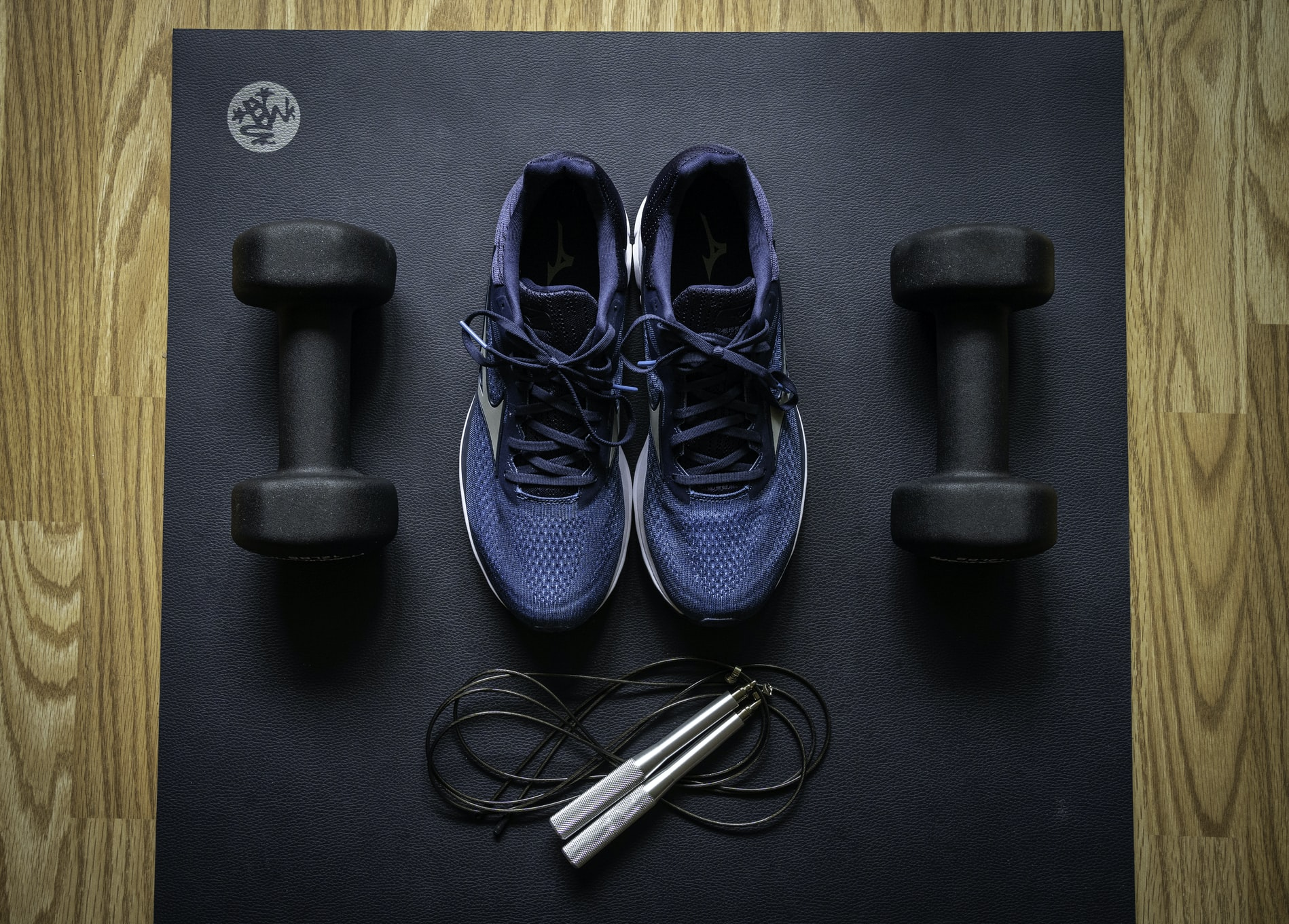 A pair of dumbbells, a jump rope, and a pair of blue shoes on a black exercise mat
