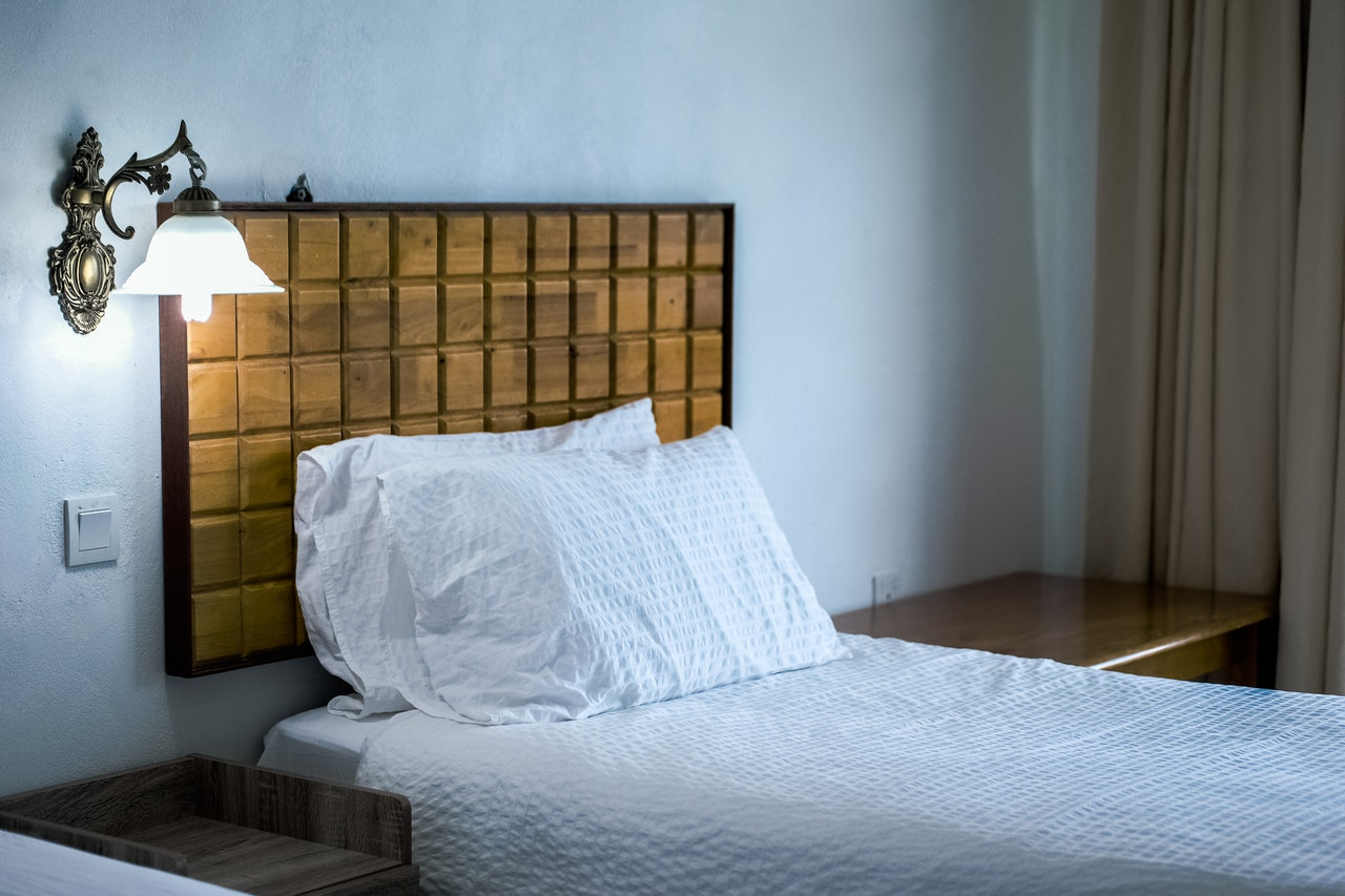 Wooden headboard on bed with white bedding