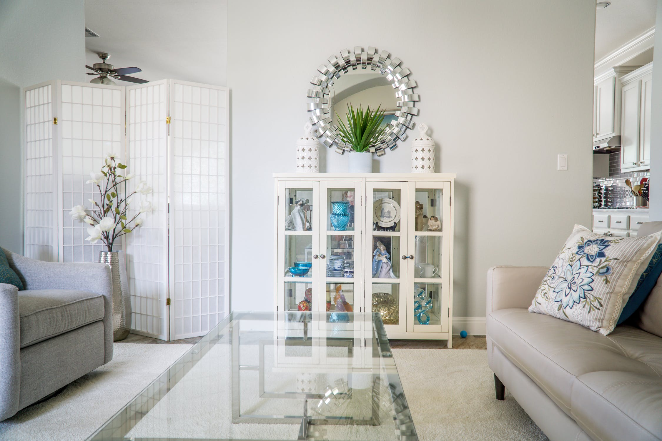 n all-white living room with a glass coffee table and a vintage white cabinet.