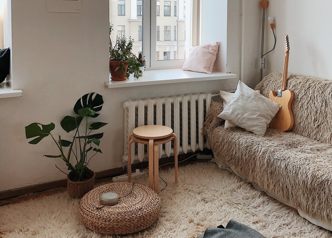 A warm sitting area overlooking a window with a shaggy couch and a guitar