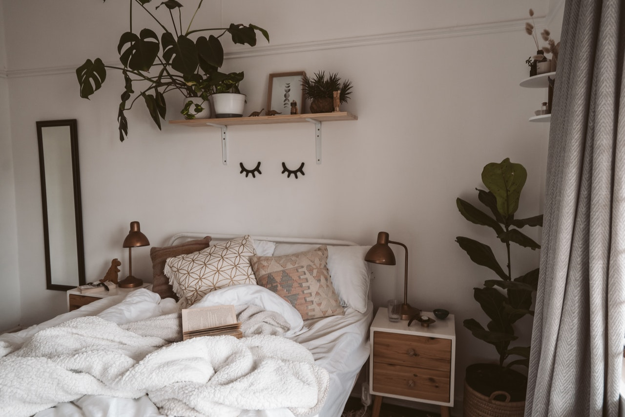 Cozy bedroom with rug, blankets and cushions