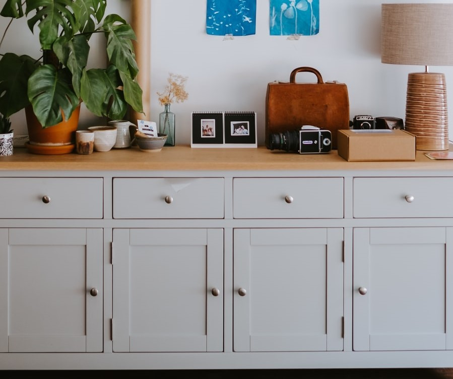 A grey wall cabinet with a wooden top and multiple drawers and storage sections