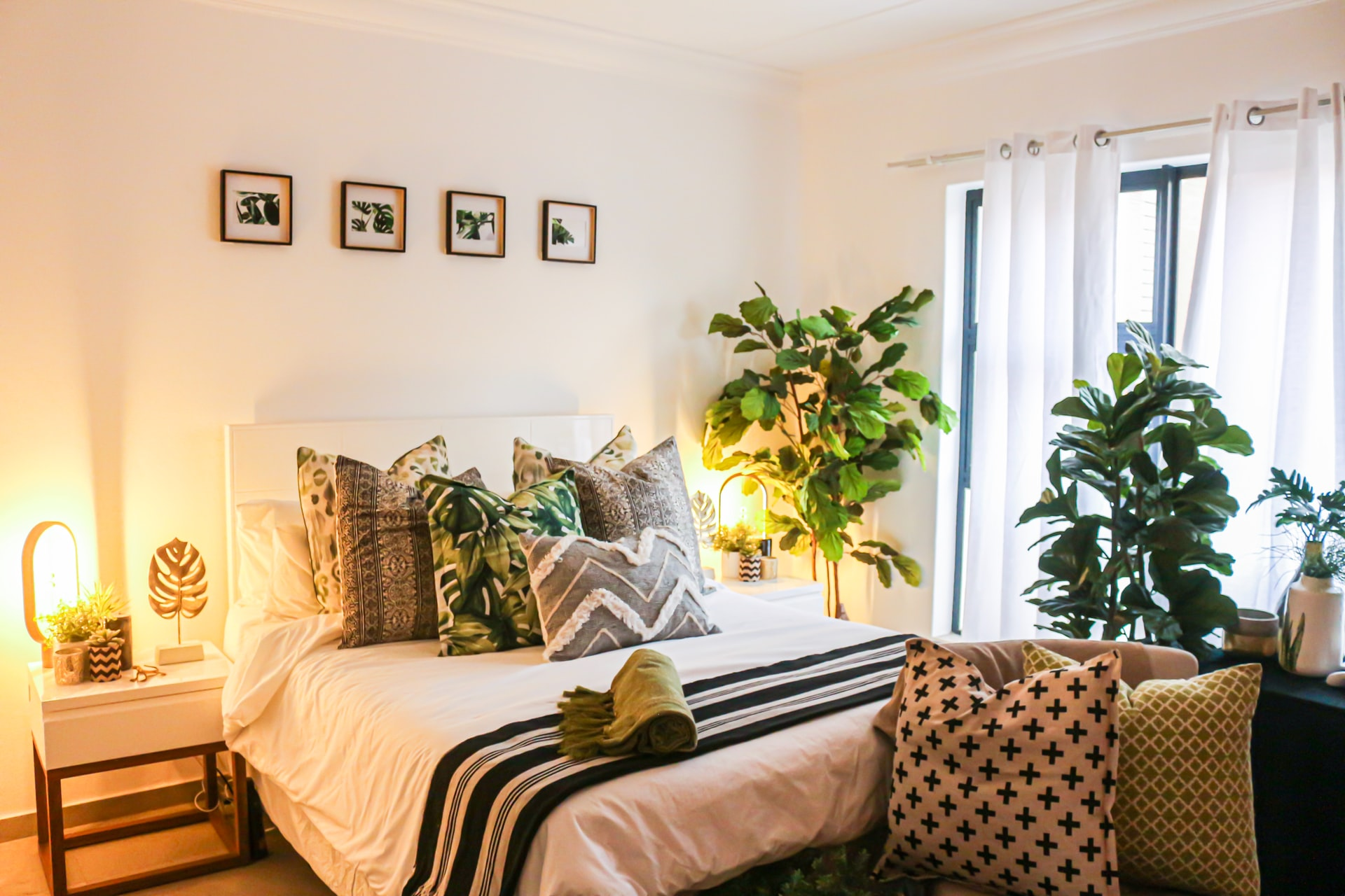 A bedroom with a neutral color scheme, textured furnishings, lots of greens, and abundant natural light
